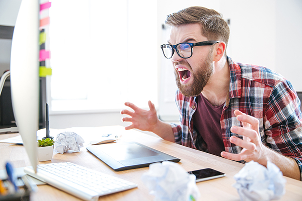 Frustrated man yelling at his computer.