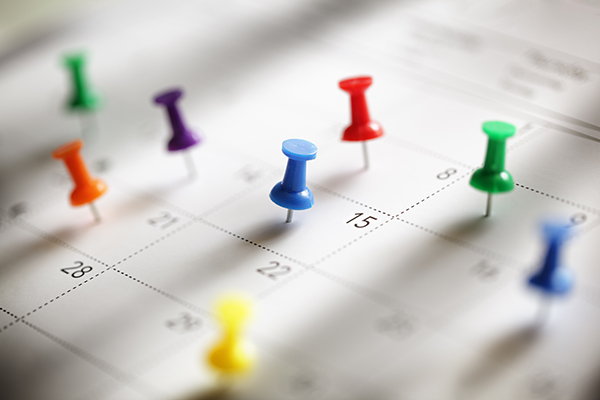 Calendar with various colored pins, noting different posts on different days.